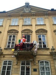 A couple of creepy looking dolls casually hanging off a balcony.